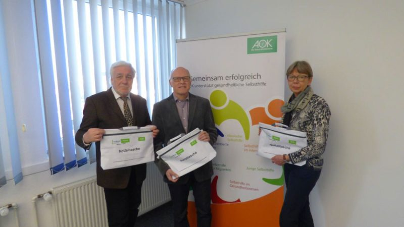 Norbert Klapper, Reiner Krauße und AOK-Mitarbeiterin Annette Jandaurek freuen sich, jetzt alle Mitglieder des Parkinson-Forums mit der Notfalltasche <a href=