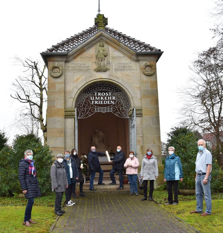 Personen stehen vor einer Kapelle