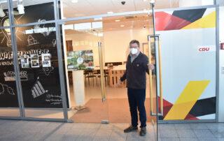 Stefan Wolters öffnet Tür von den Räumen und steht im Eingang
