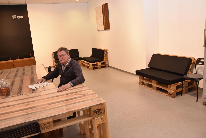 Stefan Wolters sitzt an einem Tisch aus Europaletten ind den neuen Räumen